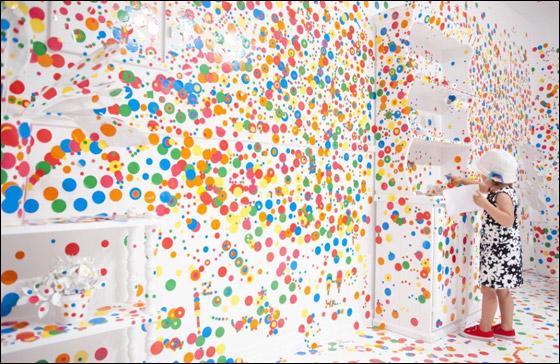 بالصور.. أطفال يغطون غرفة ناصعة البياض بالاف الملصقات الملونة!