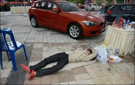 """صيني الصق يده بسيارة """"بي ام دبليو"""" 87 ساعة ليفوز بها!"""