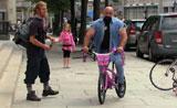 رجل عملاق يقود دراجة فتيات صغيرة